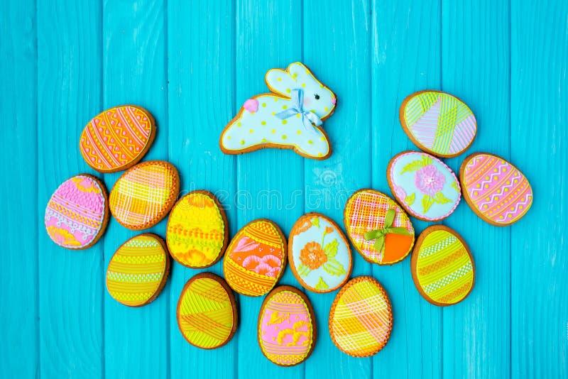 与结冰的自创曲奇饼以复活节的一个鸡蛋的形式 在蓝色背景的可口复活节曲奇饼 色的釉 免版税库存图片