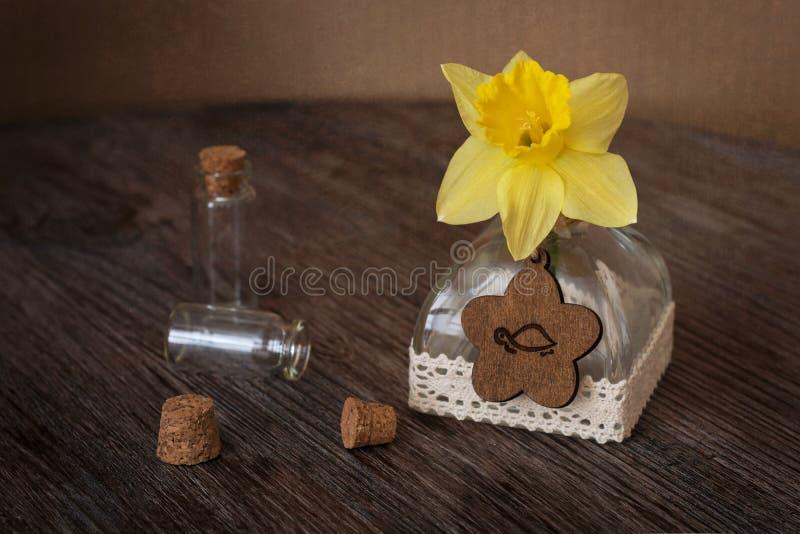 与水仙和小瓶的静物画 在一个瓶的水仙在一张木桌上 免版税库存图片