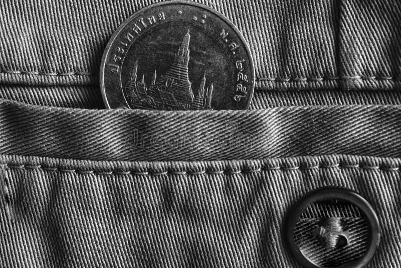 与10在牛仔布牛仔裤的口袋的泰铢的衡量单位的泰国硬币有按钮的,单色射击 库存照片