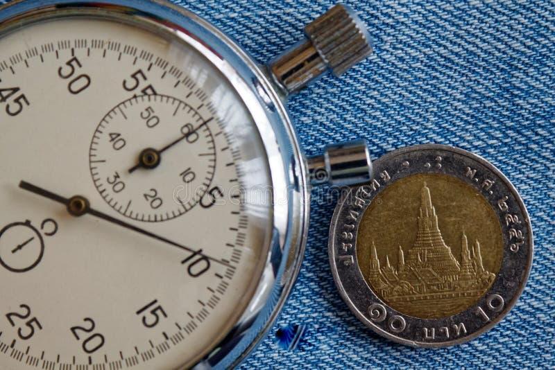 与10在蓝色被佩带的牛仔裤背景-企业背景的泰铢(后部)和秒表的衡量单位的泰国硬币 图库摄影