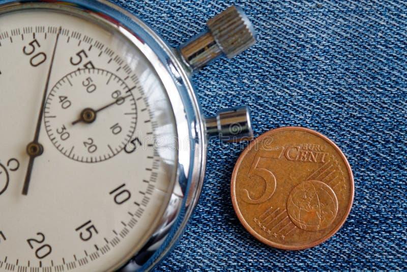 与5块欧分和秒表的衡量单位的欧洲硬币在破旧的蓝色牛仔布背景-企业背景 免版税库存照片