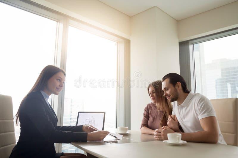 与年轻夫妇的房地产开发商会议,申请mortga 免版税图库摄影