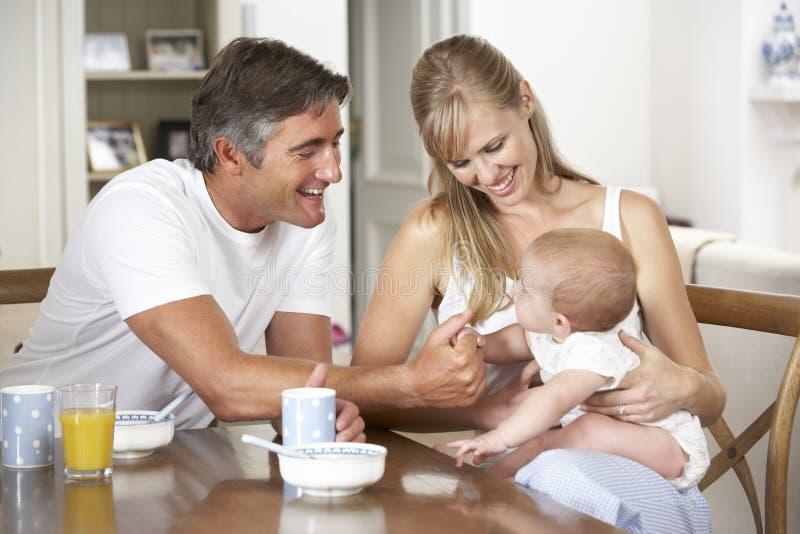 与婴孩的家庭食用早餐在厨房一起 库存照片