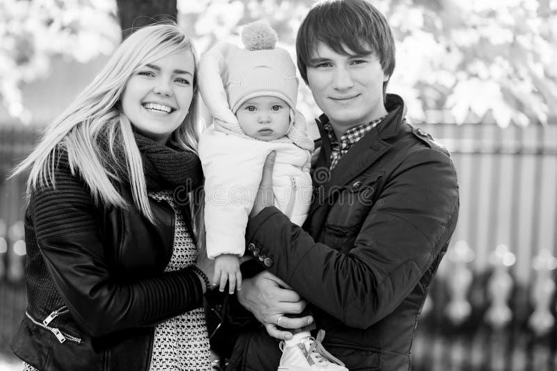 与婴孩的年轻家庭在秋天公园 黑的白色照片 免版税库存照片