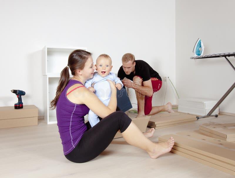 与婴孩移动的年轻家庭 库存图片