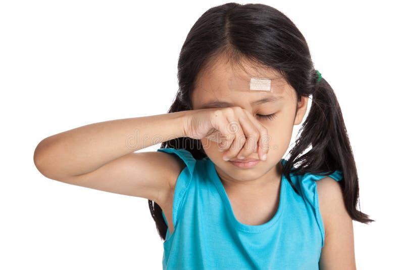 与绷带的小的亚洲女孩啼声在前额 库存照片