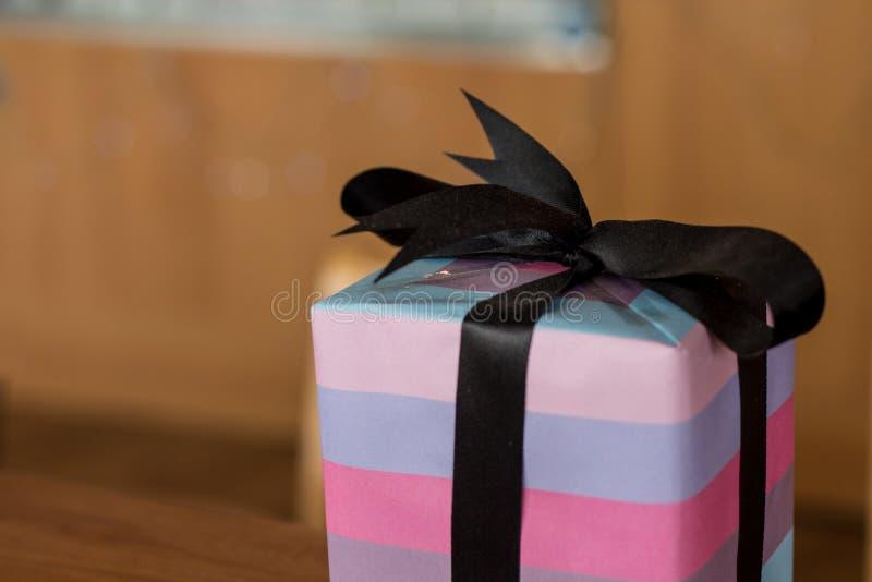 与黑弓和紫色桃红色包裹的papp的一个圣诞节礼物 免版税库存图片