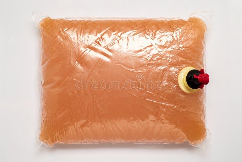 与轻拍的塑料袋有很多苹果汁 库存图片
