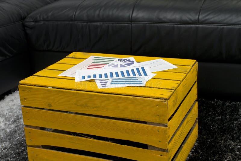 与财政图表的黄色咖啡桌 免版税库存图片