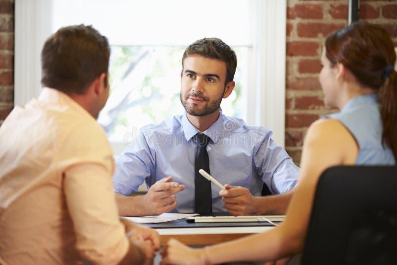 与财政顾问的夫妇会谈在办公室 免版税库存照片