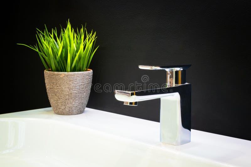 与水晶把柄的豪华龙头搅拌器在一个白色水槽在一个美丽的黑暗的卫生间里 免版税库存图片