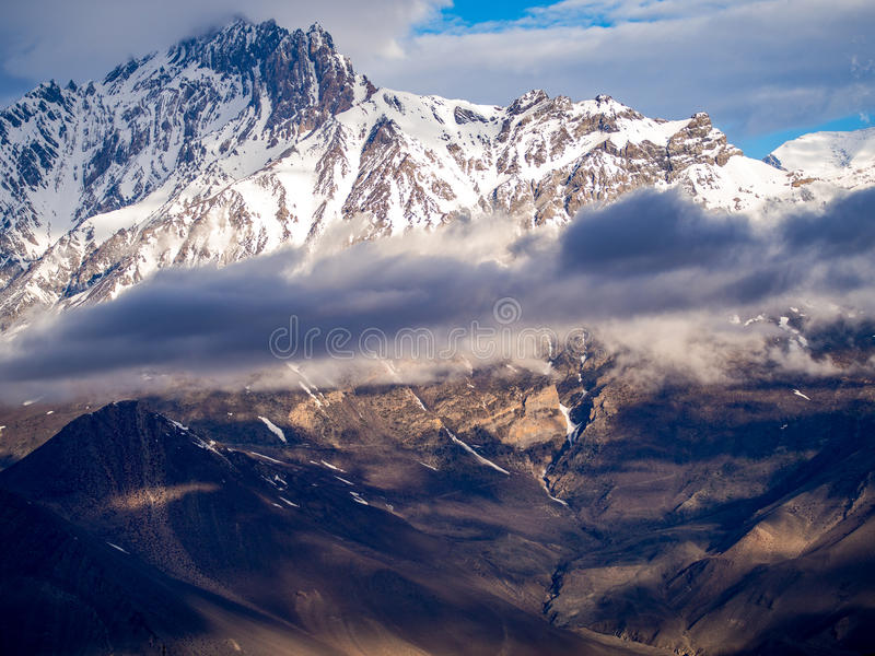 与阴暗天气的斯诺伊山在Muktinath 库存图片