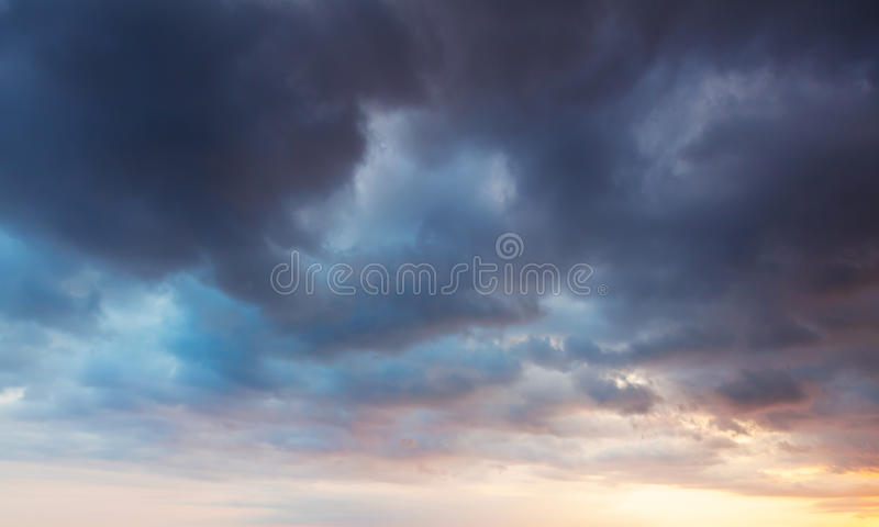 与黑暗的云彩的五颜六色的剧烈的天空在早晨 免版税库存图片