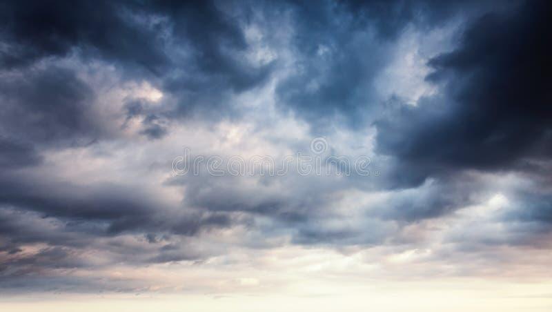 与黑暗的云彩的五颜六色的剧烈的天空 免版税库存照片