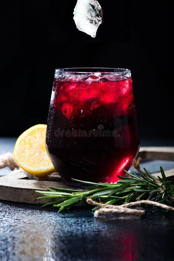 与黑暗的无核小葡萄干或樱桃饮料的玻璃 图库摄影