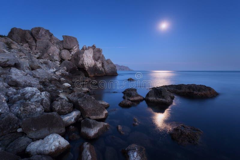 与满月、月球道路和岩石的五颜六色的夜风景在夏天 在海的山风景 库存照片