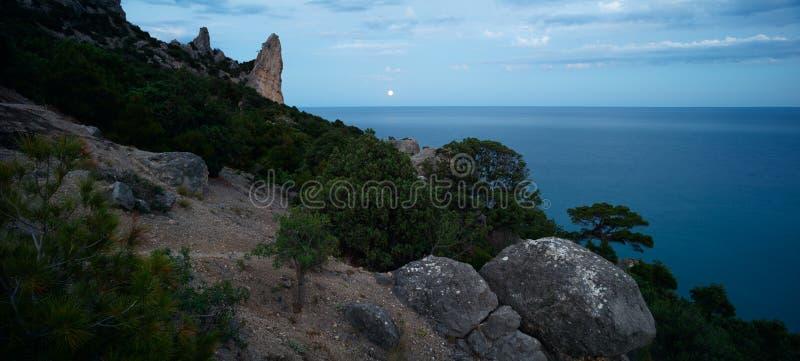 与满月月球道路和岩石的五颜六色的夜风景在夏天 在海的山风景 库存图片