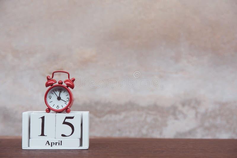 与4月的15日税天 与数字的日历木块立方体和在桌黑暗的板条木背景的红色闹钟与 免版税图库摄影