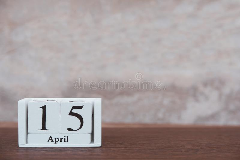 与4月的15日税天 与数字的日历木块立方体 在与拷贝空间的桌黑暗的板条木背景 库存照片