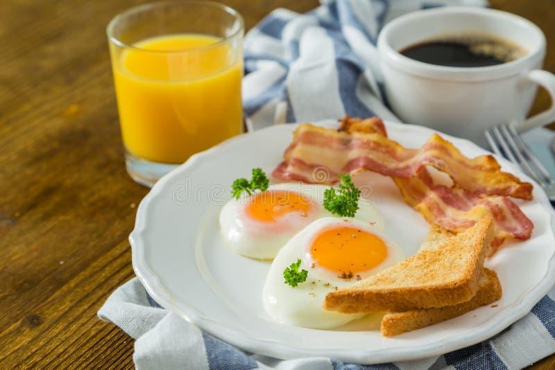 与晴朗的边的美国早餐鸡蛋、烟肉、多士、薄煎饼、咖啡和汁液 免版税库存照片