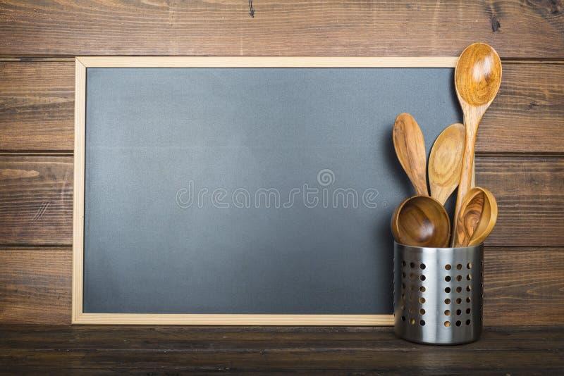 与黑板和炊事用具的木背景 库存照片
