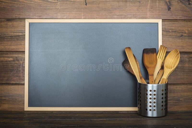 与黑板和炊事用具的木背景 免版税库存照片