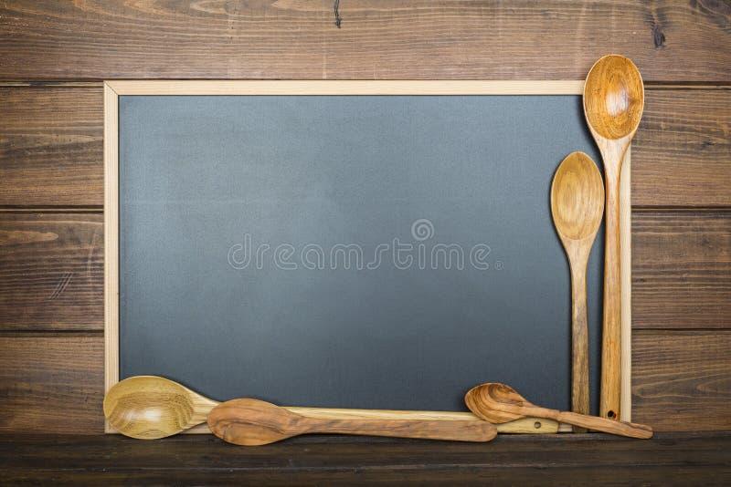 与黑板和炊事用具的木背景 免版税图库摄影