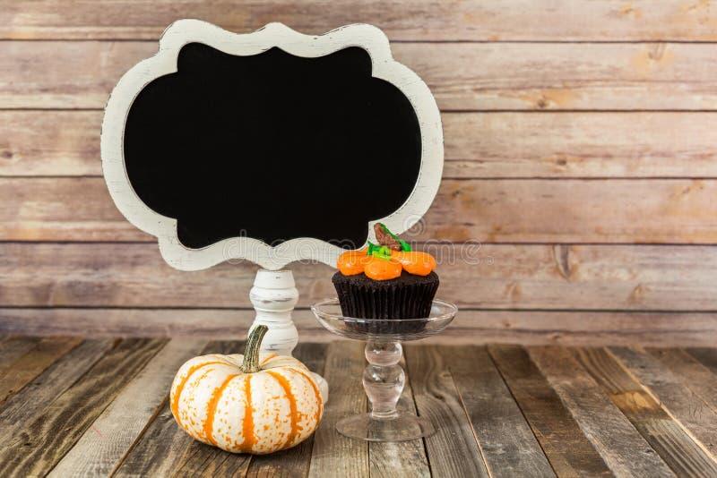 与黑板的南瓜杯形蛋糕 图库摄影