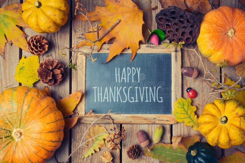 与黑板的感恩背景 秋天在木桌上的南瓜和秋天叶子 图库摄影