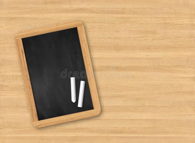 与黑板的木桌面看法 免版税库存照片