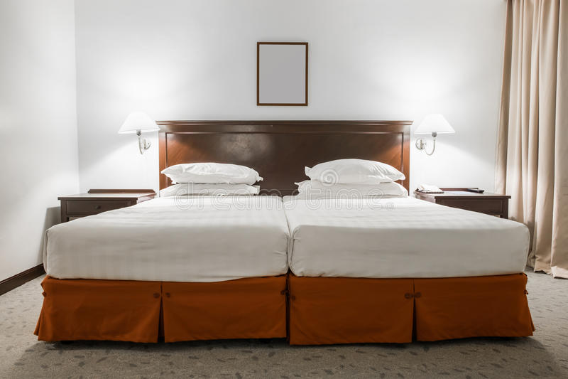 与画框的白色成对床在旅馆客房 库存照片