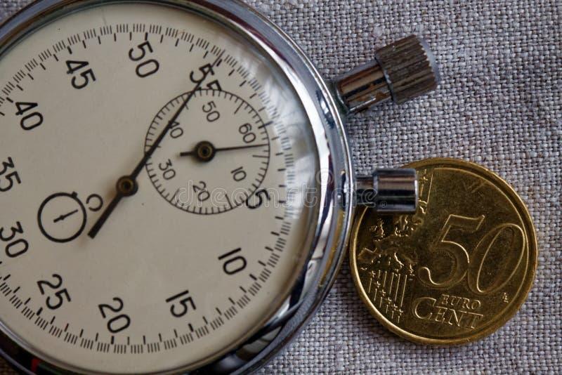 与50欧分和秒表的衡量单位的欧洲硬币在白色亚麻制背景-企业背景 免版税库存照片