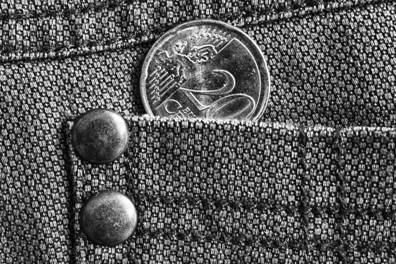 与20欧分的衡量单位的欧洲硬币在牛仔布牛仔裤的口袋,单色射击的 免版税库存图片