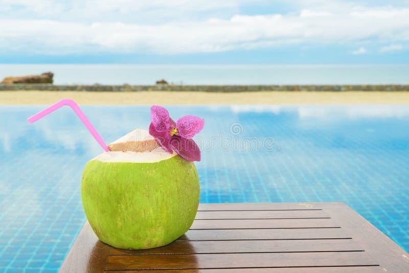 与水池的热带新鲜的椰子鸡尾酒和海滩在海洋,普吉岛,泰国 图库摄影