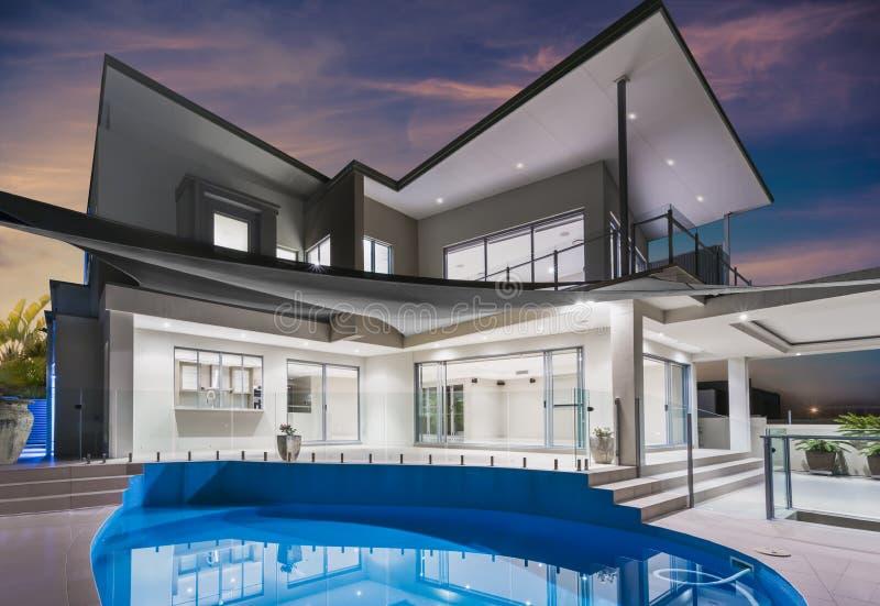 与水池的豪宅和在黄昏的美丽的天空 免版税库存照片