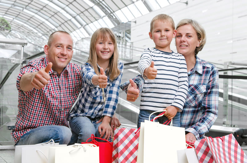 与购物袋的家庭在显示拇指的购物中心 免版税库存图片