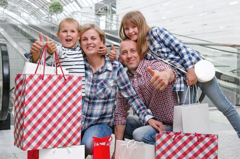 与购物袋的家庭在显示拇指的购物中心 库存照片