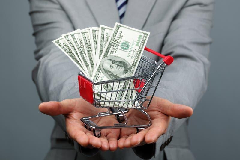与购物车和金钱的商人 免版税库存照片