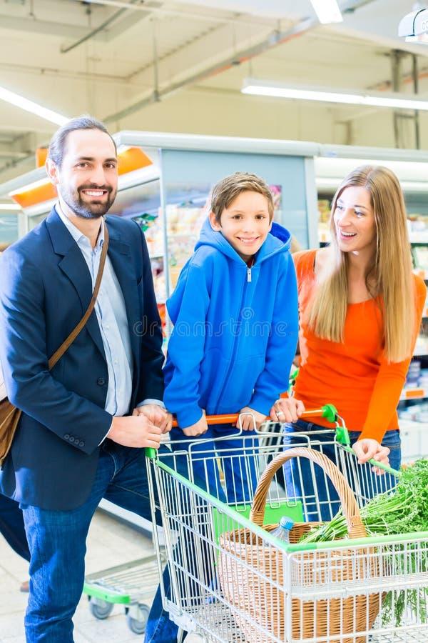 与购物车的家庭在杂货店 免版税库存图片