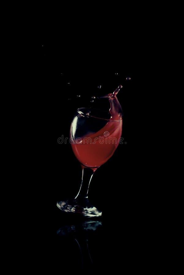 与玻璃冲击的红色流体 免版税库存照片