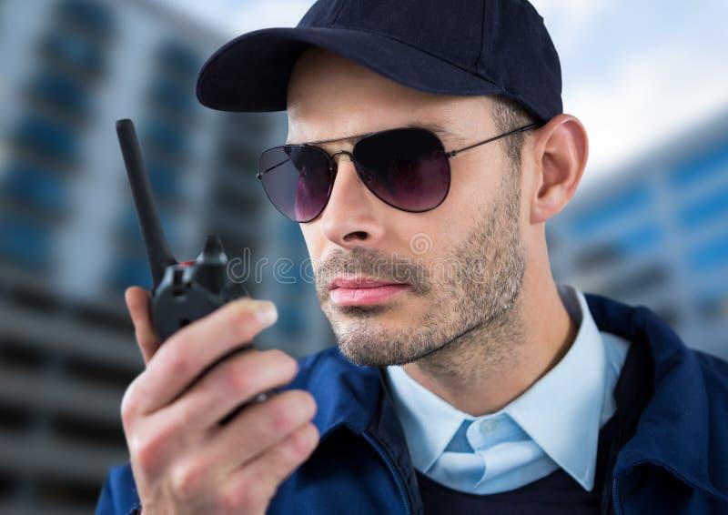 与玻璃和携带无线电话的严肃的治安警卫有被弄脏的修造的背景 免版税库存图片