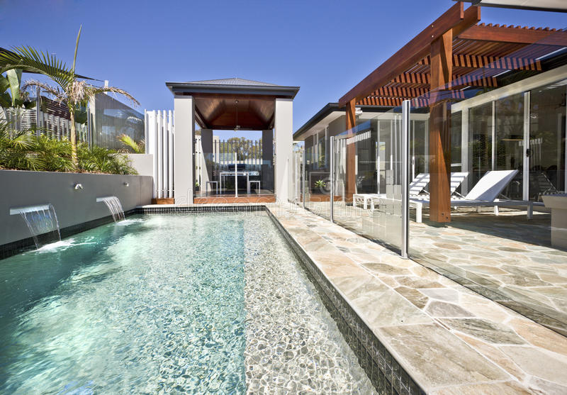 与玻璃盖和木露台的现代游泳池边 免版税库存照片