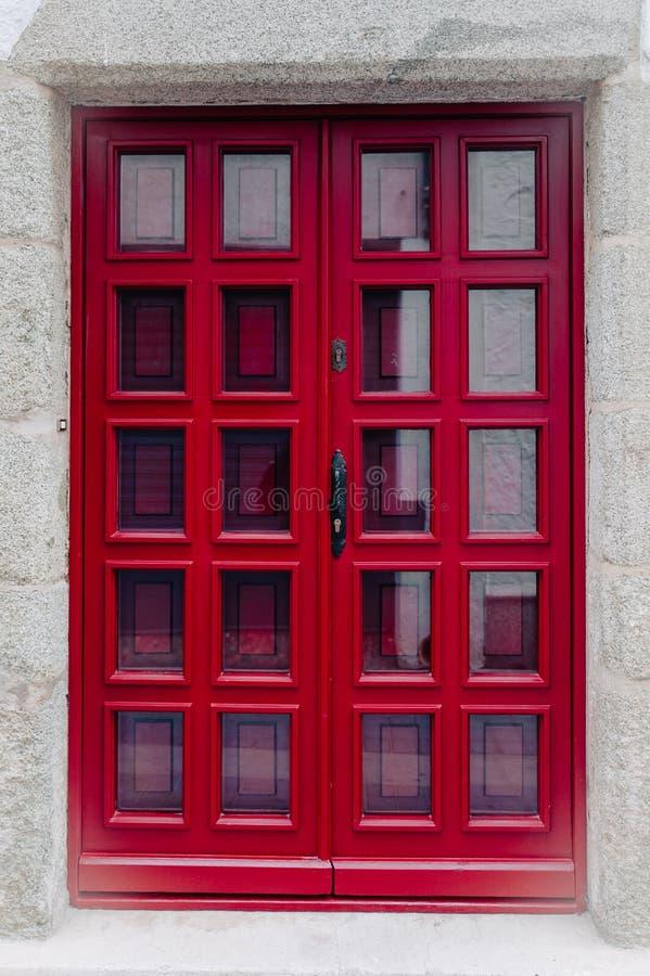 与玻璃窗的红色门 免版税库存照片