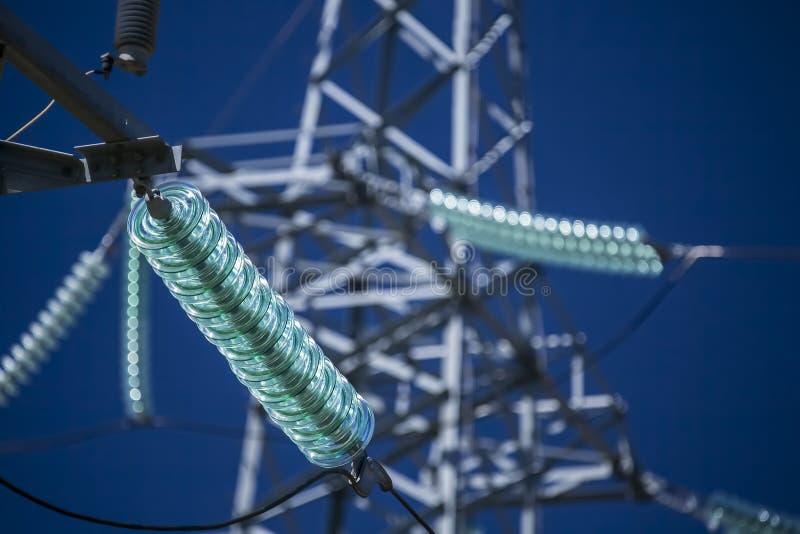 与玻璃绝缘体的高压传输力量塔 免版税图库摄影