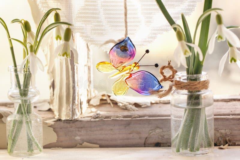 与玻璃蝴蝶和snowdrops的Iterior窗口 免版税库存照片
