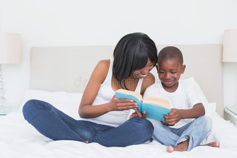 与他的儿子的俏丽的母亲读书在床上 库存图片