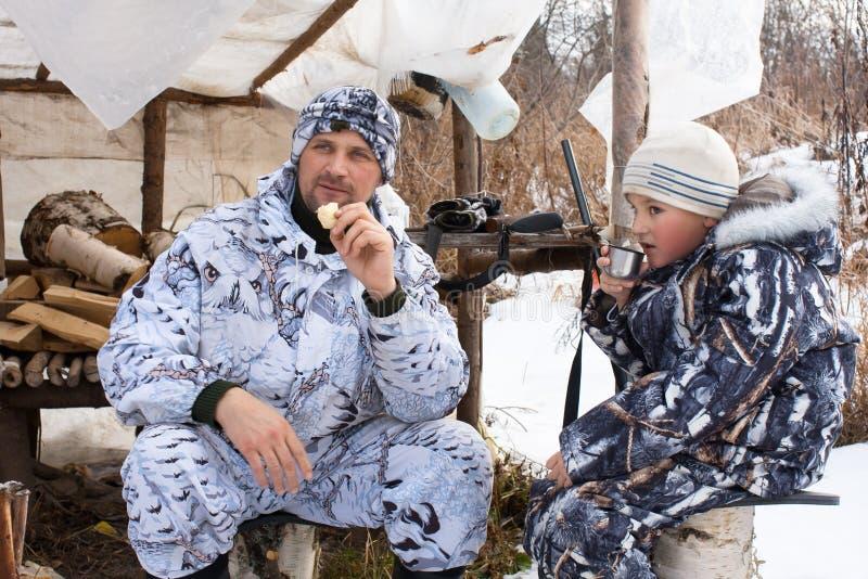 与他的儿子的猎人在狩猎帐篷下的休息期间 库存图片