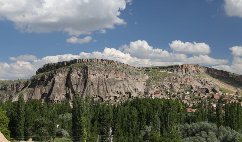 与洞的小山在Guzelyurt镇,卡帕多细亚 库存照片