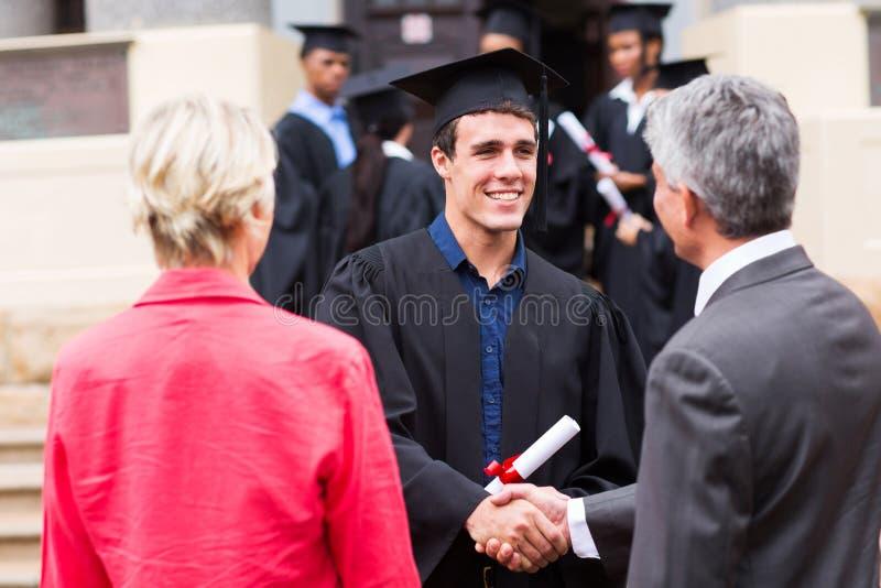 与他的父亲的男性毕业生握手 库存图片