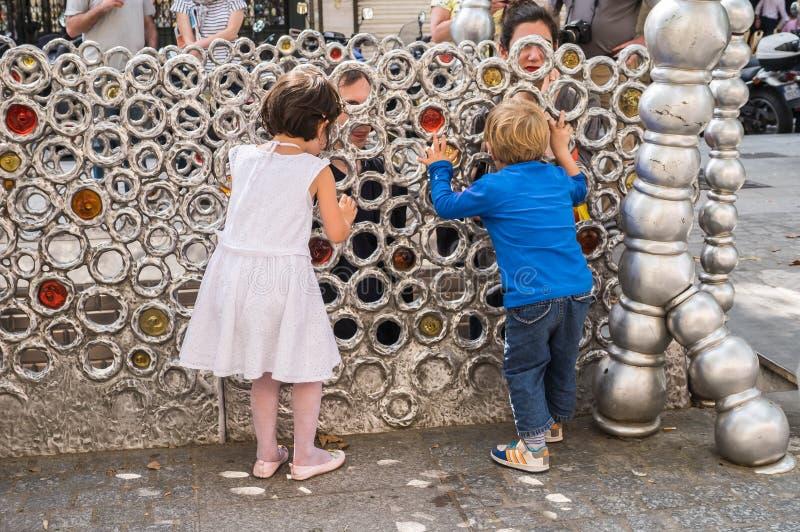 与他们的父母的年轻儿童游戏捉迷藏通过圆环 库存照片